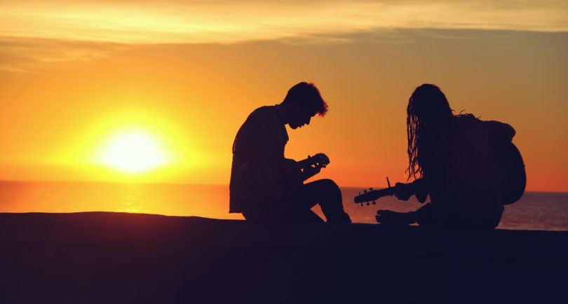 Boy and a girl playing guitar at sunset.