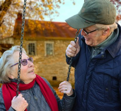 A woman sits on a swing and a man stands next to her, both are enjoying their retirement.
