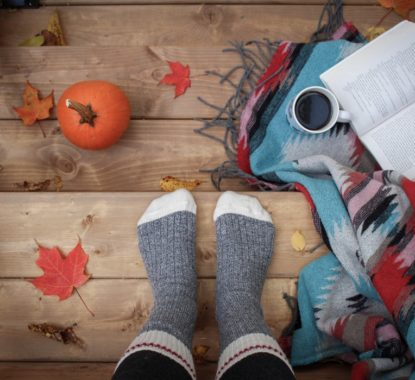 person standing with fall leaves around them, coffee, and a book on a blanket