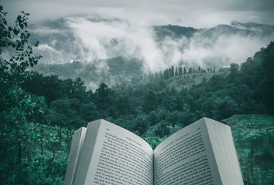 Book open in front of mountains and forests
